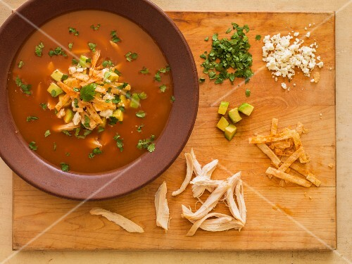 Tortilla soup on a chopping board with garnishes (chicken, tortilla strips, avocado, coriander and cheese)