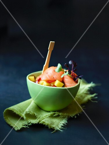 A bowl of raw salmon with mango salsa