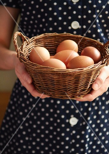 A woman holding a basket of fresh chicken's eggs