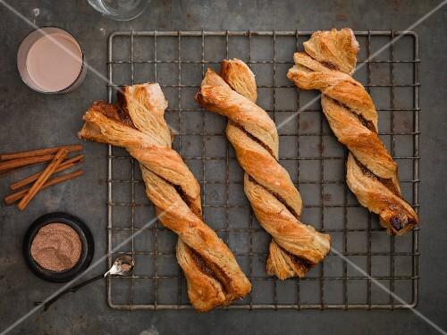 Cinnamon twist pastries on a cooling rack, cinnamon sticks and cinnamon-sugar