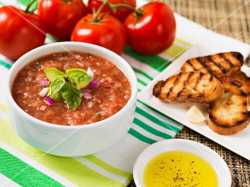 Gazpacho garnished with avocado, red onions and basil, olive oil, crostini and fresh tomatoes