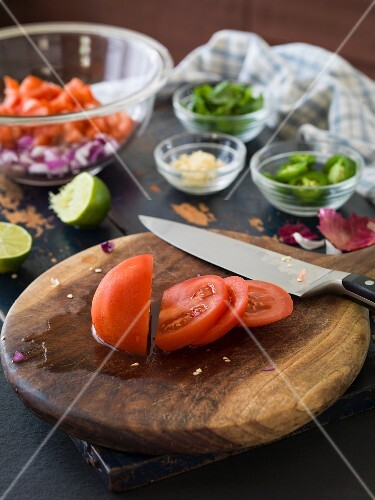 Freshly sliced tomatoes on a chopping board to be used to make tomato salsa