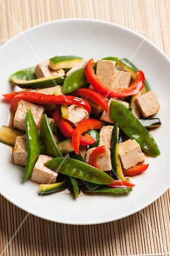 Stir-fried tofu cubes and vegetables (mange tout, courgette and red peppers) with soy sauce