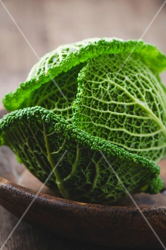 A savoy cabbage in a wooden bowl