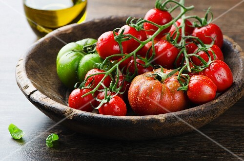 Various freshly washed tomatoes in a wooden bowl