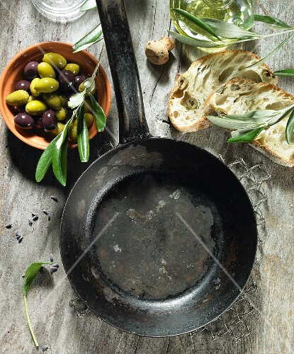 An empty pan, sage, black and green olives, olive oil, an olive sprig, olive ciabatta and lavender