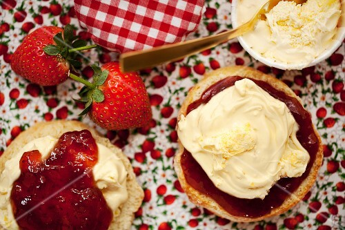 A scone split in half topped with clotted cream and strawberry jam