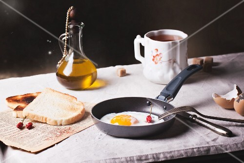 Breakfast with a fried egg, toast, chilli peppers and olive oil