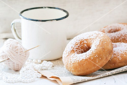 Sugar doughnuts and a white vintage mug on an old newspaper