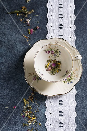 A herbal tea mixture with various flowers in an old-fashioned cup