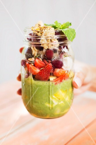 A hand holding a jar of breakfast parfait with berries and pumpkin seed milk