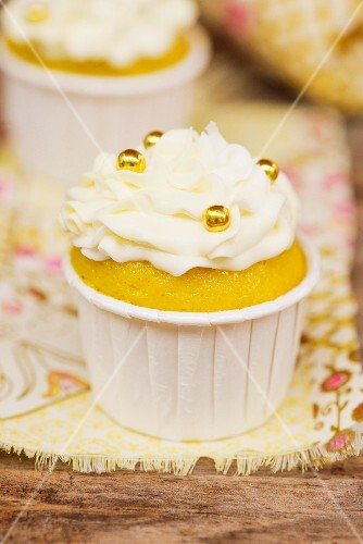 A cupcake decorated with buttercream and golden pearls