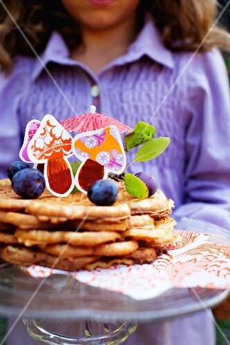 A girl holding a plate of waffles with plums and colourful paper mushrooms