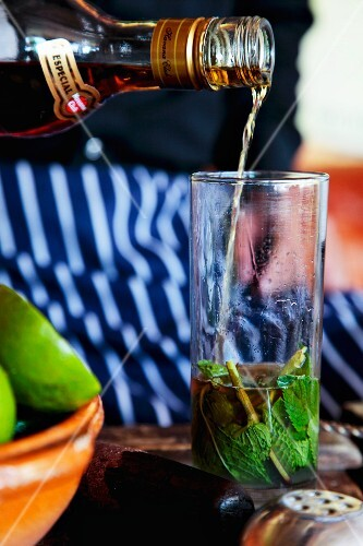 A mojito being made (brown rum being added)