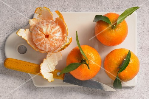 Mandarins, whole and peeled, on a chopping board