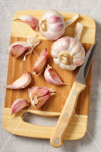 Garlic bulbs and garlic cloves on a chopping board