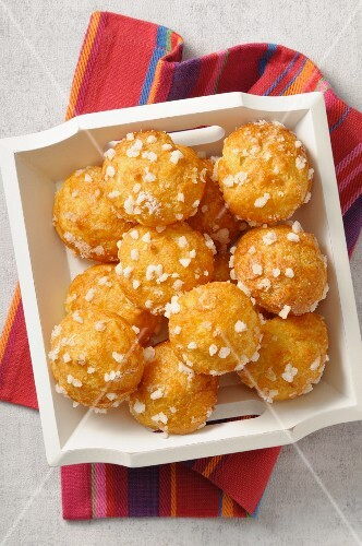 Chouquettes with crystal sugar on a wooden tray