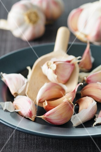 Garlic on a wooden scoop on a plate