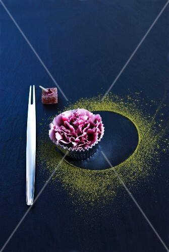 An Oriental fork next to a carnation in a muffin case and green tea powder on a black surface