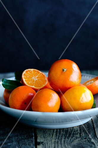 Clementines in a grey bowl on a wooden surface