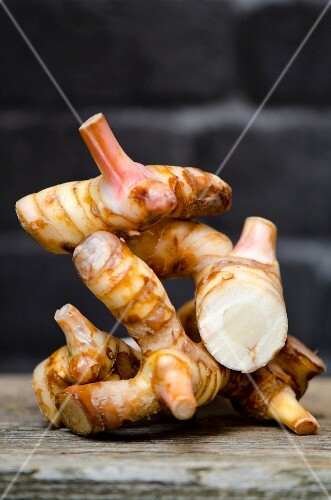 Fresh galangal roots on a wooden board