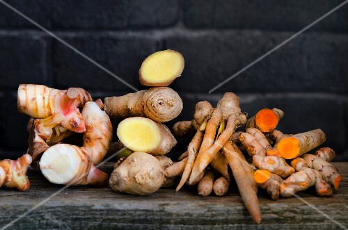 Fresh galangal, fingerroots, turmeric and ginger on a wooden board