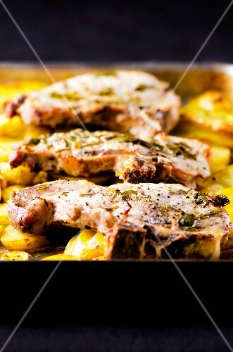 Grilled pork steaks with lemon and sage served on roast potatoes