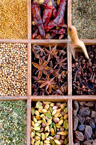 Various spices in a wooden box (seen from above)