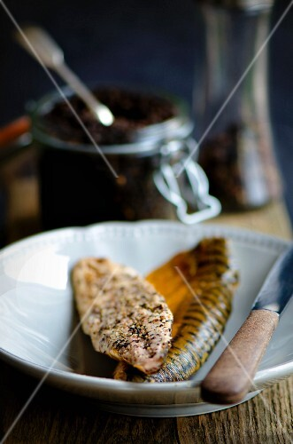 Smoked peppered mackerel fillets in front of a jar of peppercorns