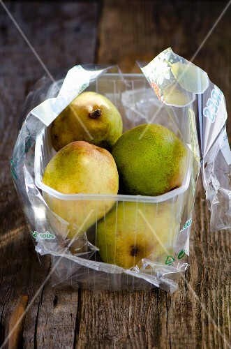 Pears in a plastic box wooden surface