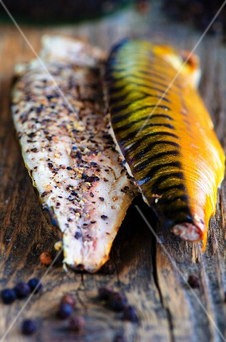 Smoked mackerel fillets with pepper on a pine wood board