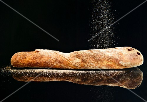 A baguette being sprinkled with flour