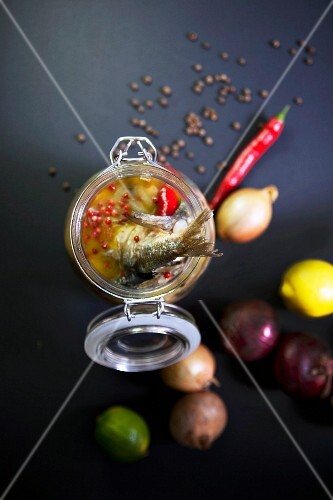 Pickled fried herring in a jar with lemons, limes, chilli peppers and onions