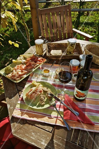 A snack with red wine on a garden table