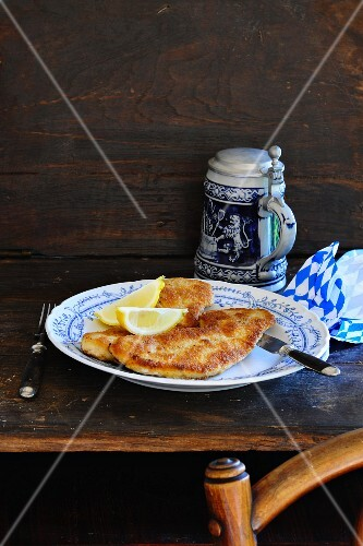 Wiener Schnitzel (breaded veal escalope from Vienna) with lemon wedges on a rustic table with a tankard of beer in the background