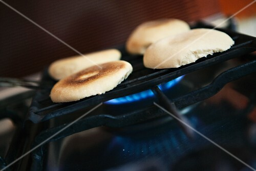 Halved bread rolls on a grill