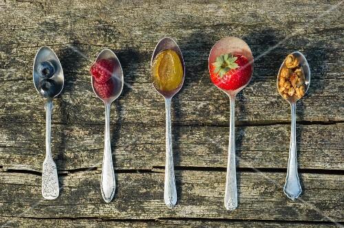 Fresh fruit and nuts on spoons depicting muesli ingredients