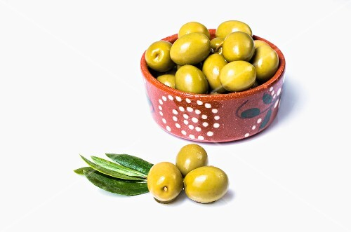 A bowl of green olives and some next to it