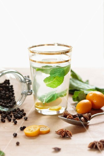 A glass of peppermint tea with mint leaves, a kumquat and spices