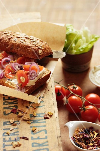 A slice of bread topped with cream cheese, tomatoes, onions and flowers