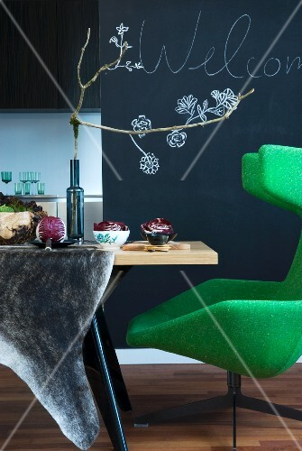 Green, designer wingback chair, dining table and autumnal table decoration with flowers drawn on wall painted with chalkboard paint in background