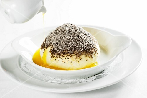 Melted butter being poured over a Germknödel (yeast dumpling filled with plum jam) topped with poppy seeds