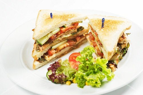 A club sandwich served with salad