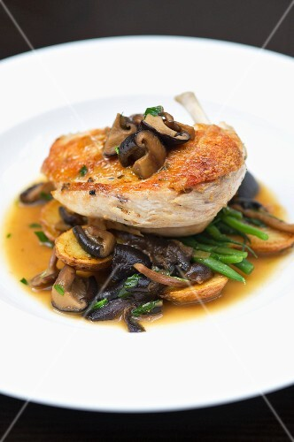 Chicken breast served with a mushroom sauce, potatoes and green beans