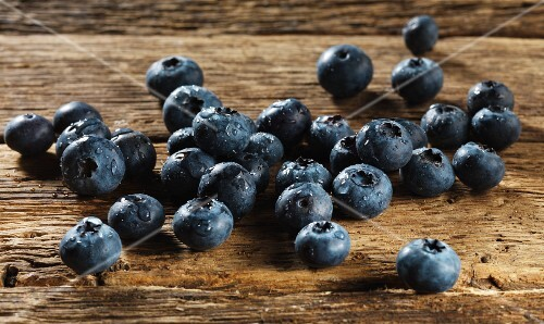 Freshly washed blueberries on a wooden surface