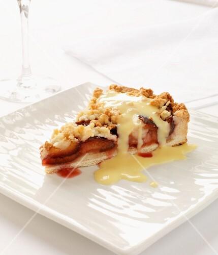 A slice of plum crumble tart with custard
