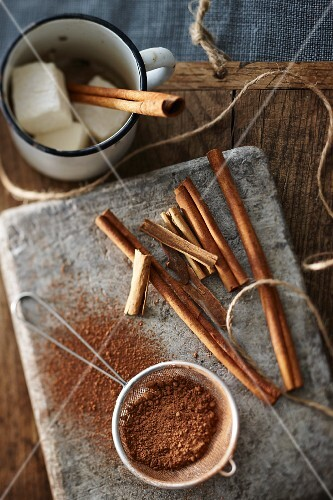 Ingredients for making cocoa with marshmallows and cinnamon sticks