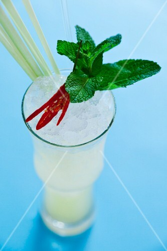 A cocktail garnished with lemongrass, mint and a chilli pepper