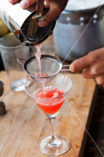 A cocktail being poured into a glass through a sieve