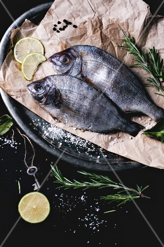 Two seabream fish with rosemary, lime and sea salt served on baking paper